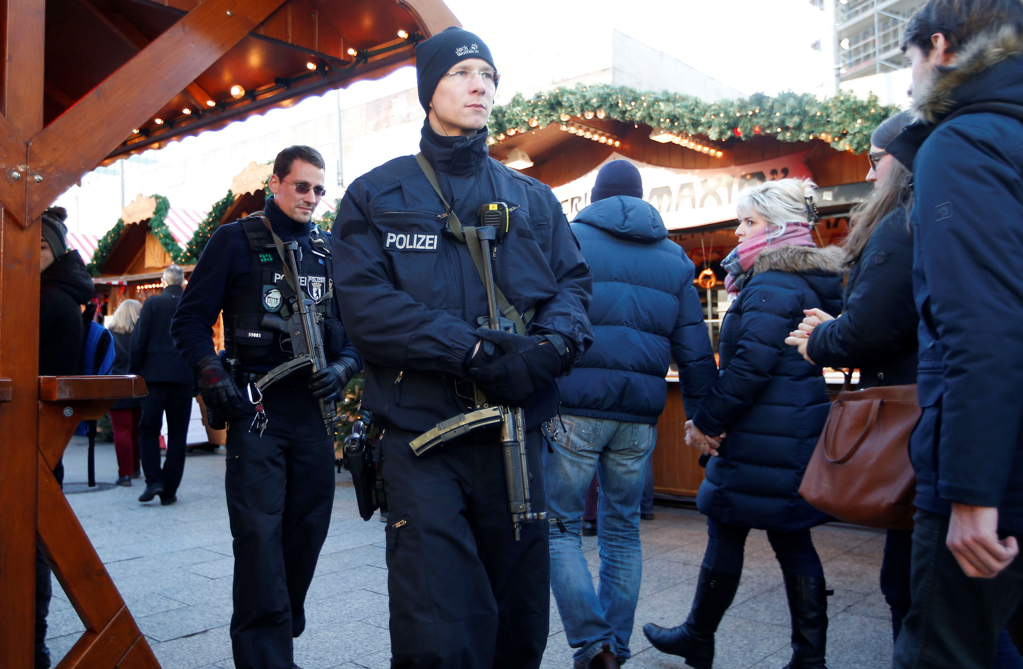 German police patrol with submachine guns at the Christmas market at Breitscheid square in Berlin, Germany, December 30, 2016, following an attack by a truck which ploughed through a crowd at the market.   REUTERS/Fabrizio Bensch - RTX2WY9P