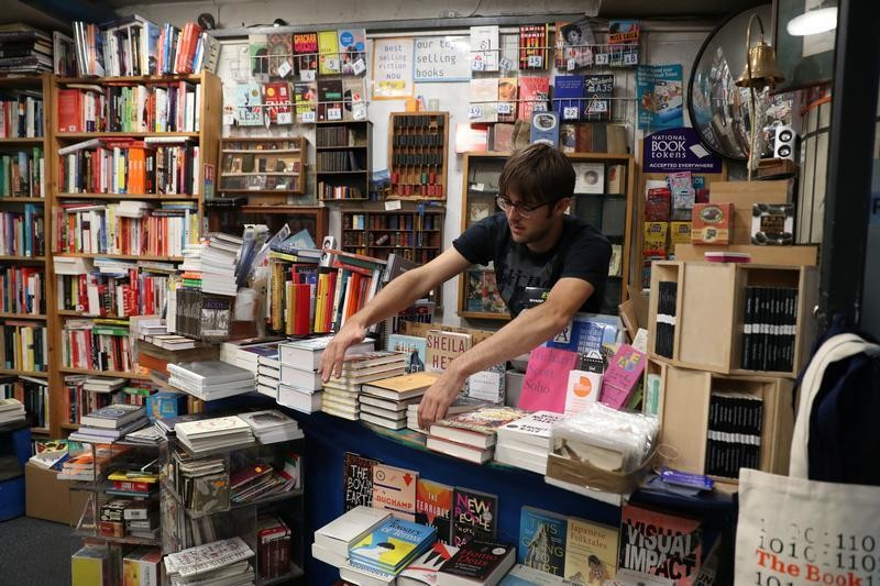 Jake, an employee of Camden Lock Books shop, arranges books, in Old Street Station, London, Britain, September 13, 2018. REUTERS/Peter Cziborra - RC14F6E729A0