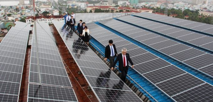a group of business people walk across a roof filled with solar panels installed