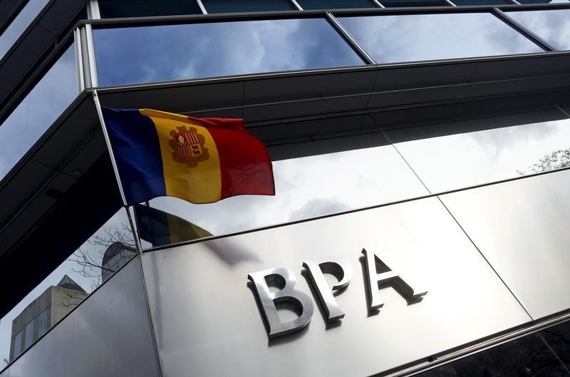 An Andorran national flag flies next to a Banca Privada d'Andorra (BPA) office in Andorra la Vella March 29, 2015. Andorra will create a 'bad bank' to group the assets of BPA linked to illicit activity, it said late on Thursday, as the principality battles to rebuild the reputation of its banking system. REUTERS/Albert Gea - GF10000043162