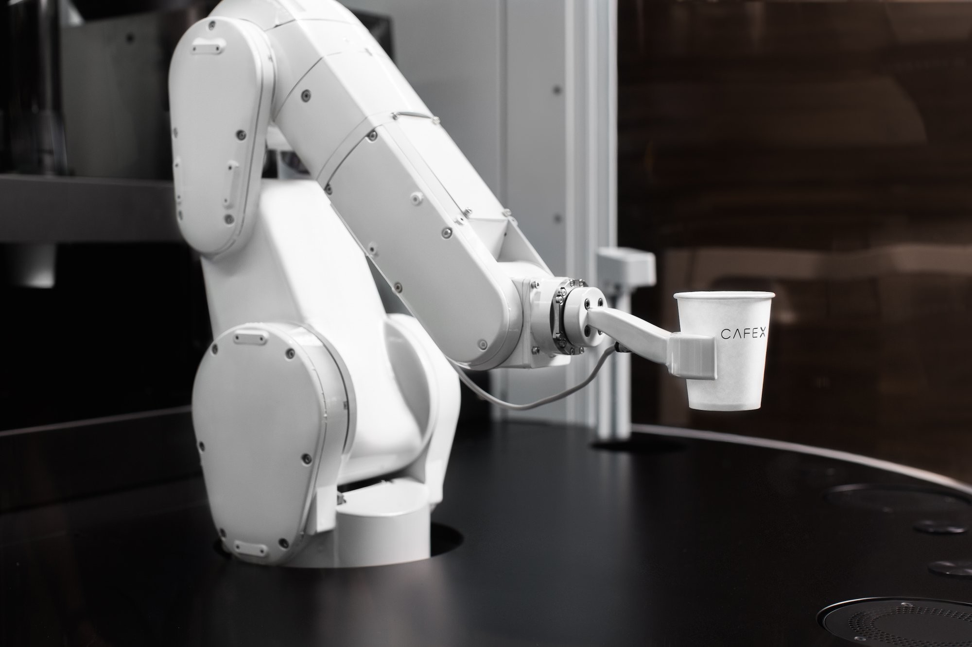 A robotic arm handles a cup of coffee at automation-powered coffee kiosk Café X in San Francisco, California.