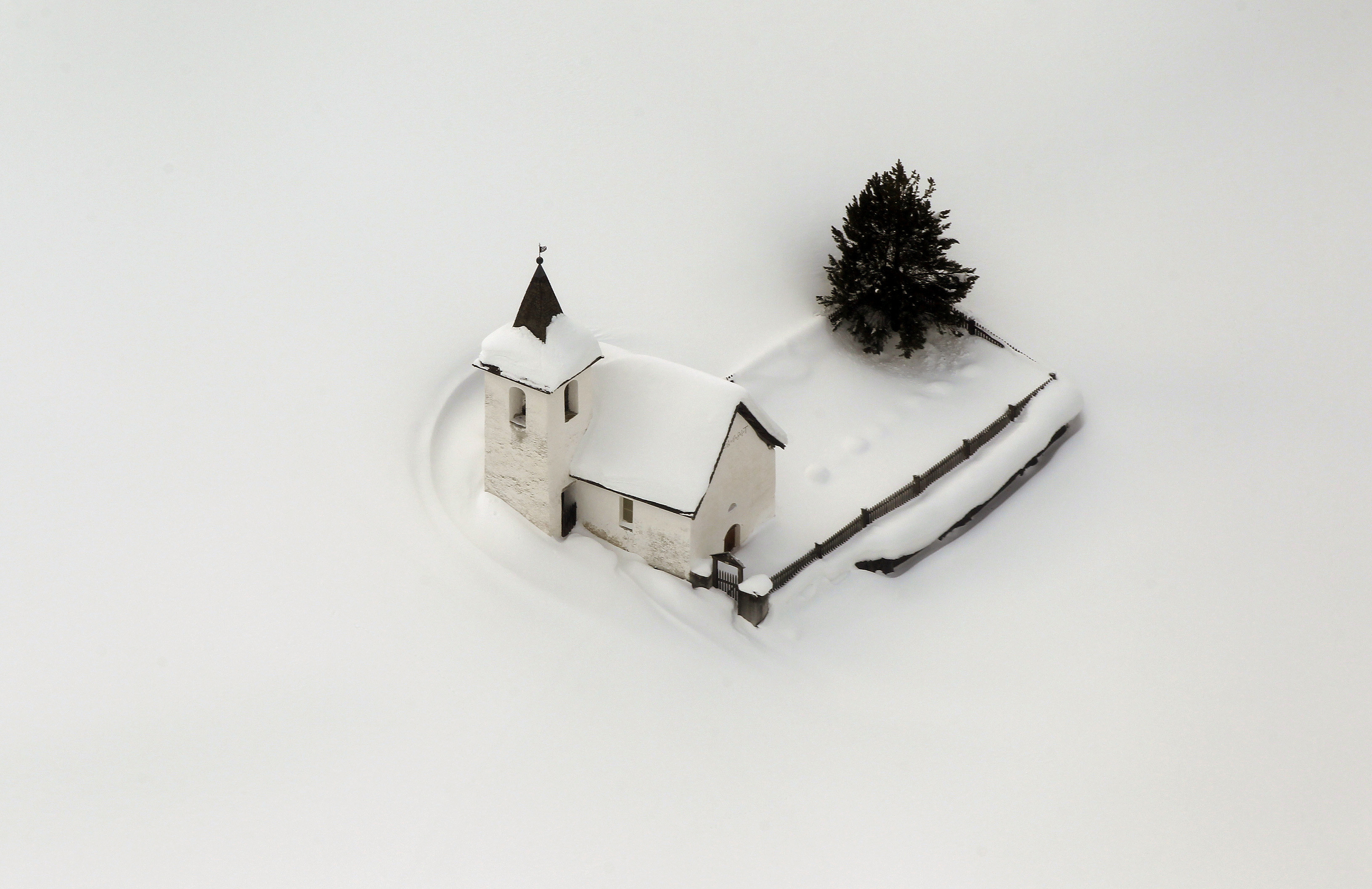 An aerial view shows the snow covered church of the village of Jenisberg near the Swiss mountain resort of Davos January 23, 2012.      REUTERS/Arnd Wiegmann (SWITZERLAND - Tags: ENVIRONMENT RELIGION TPX IMAGES OF THE DAY) - RTR2WPXX