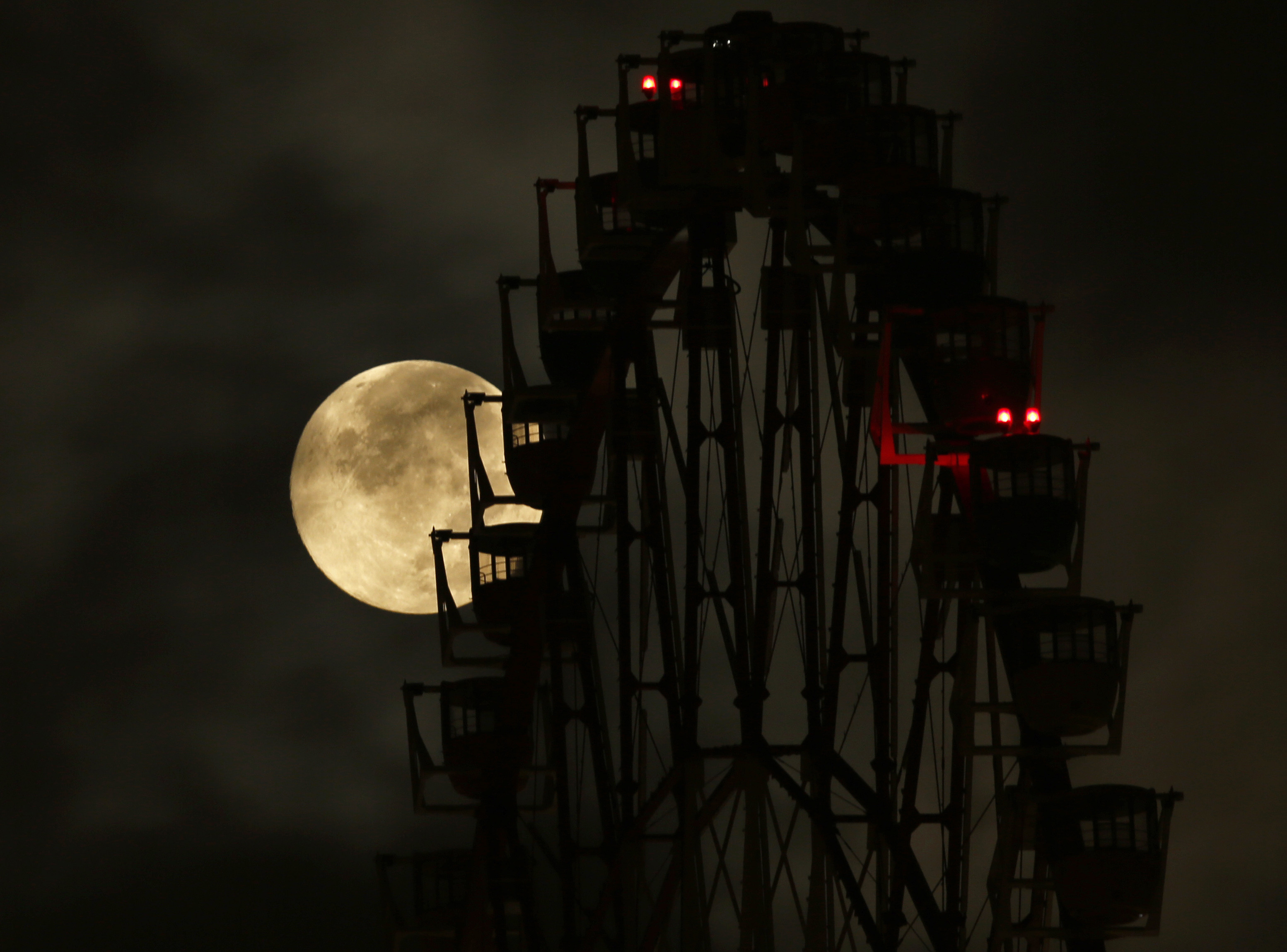 The supermoon is seen behind a ferris wheel in Tokyo August 11, 2014. The astronomical event occurs when the moon is closest to the Earth in its orbit, making it appear much larger and brighter than usual. REUTERS/Toru Hanai (JAPAN - Tags: ENVIRONMENT SOCIETY) - RTR41W7U