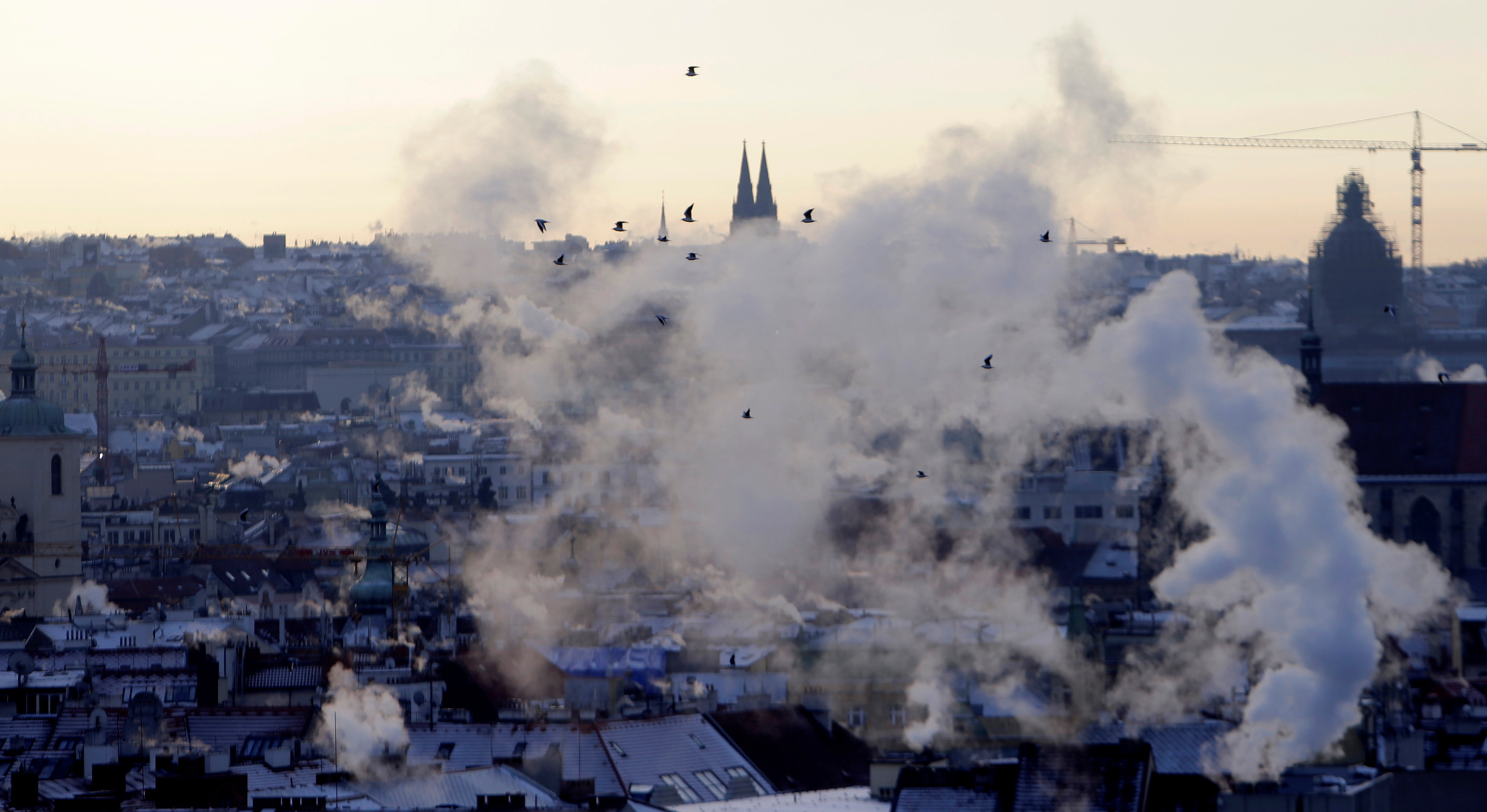 Birds fly through a smoke from chimneys billowing over the rooftops of downtown Prague as temperatures dropped to as low as minus 11 degrees Celsius (12.2 degrees Fahrenheit), Czech Republic, January 7, 2017.  REUTERS/David W Cerny - RTX2XUIZ