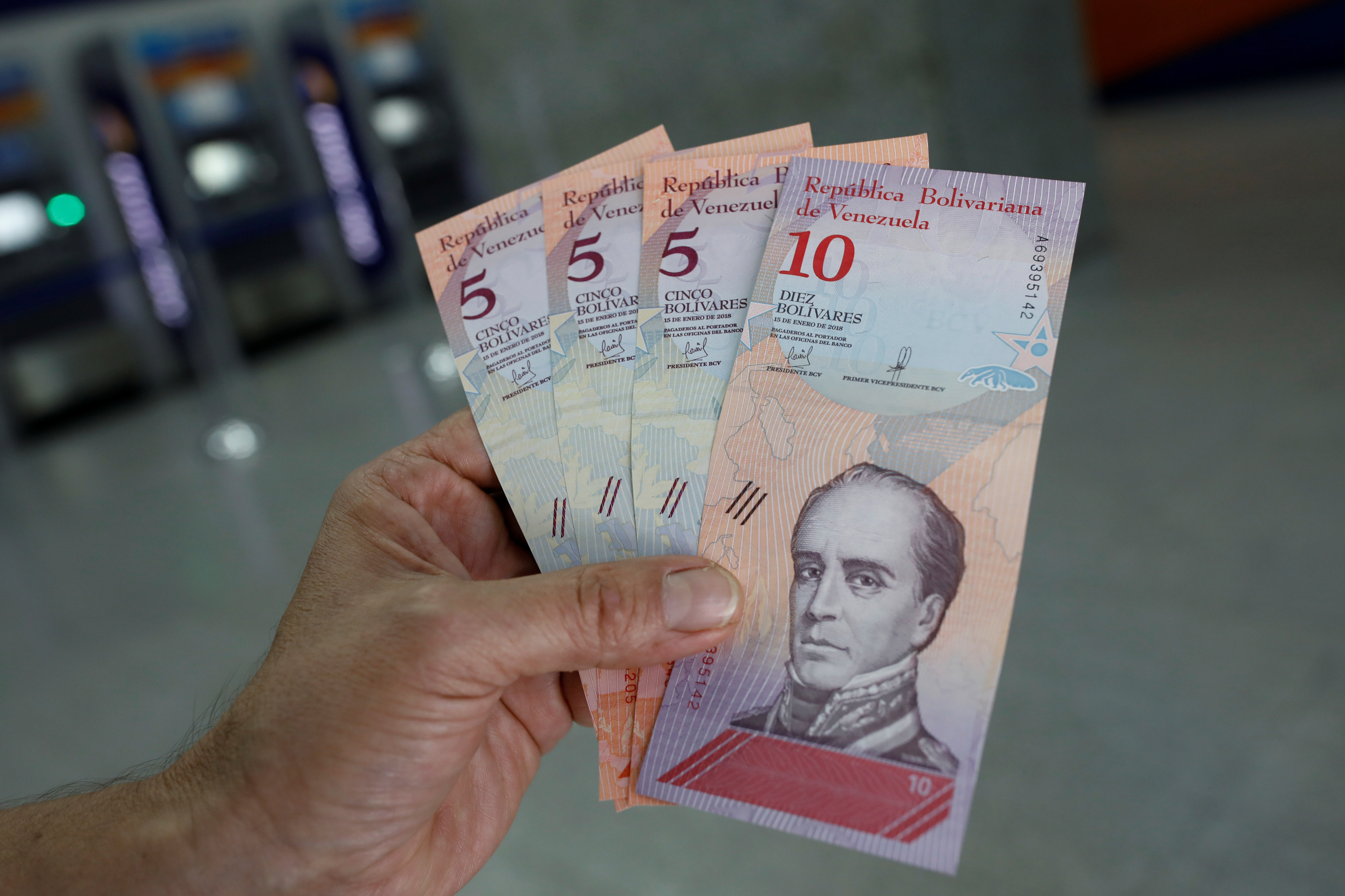 A man shows the new five and ten Bolivar Soberano (Sovereign Bolivar) bills, after he withdrew them from an automated teller machine (ATM) at a Mercantil bank branch in Caracas, Venezuela August 20, 2018. REUTERS/Carlos Garcia Rawlins - RC181067B810