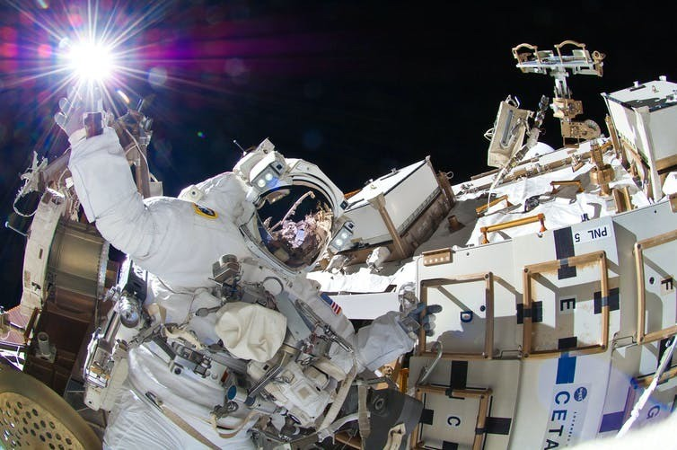 A NASA astronaut doing maintenance outside of their capsule