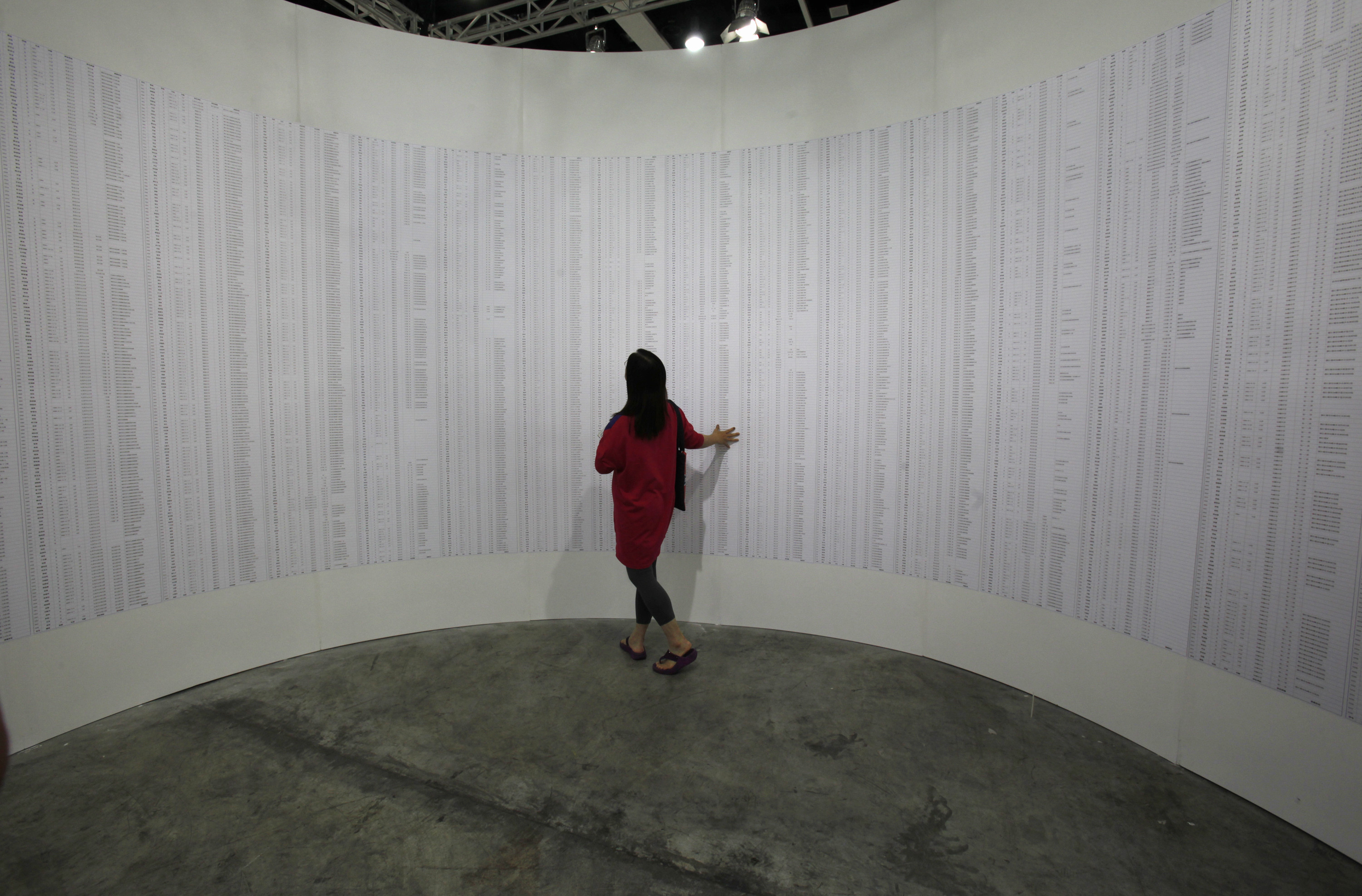 A visitor looks at the interior portion of an artwork titled