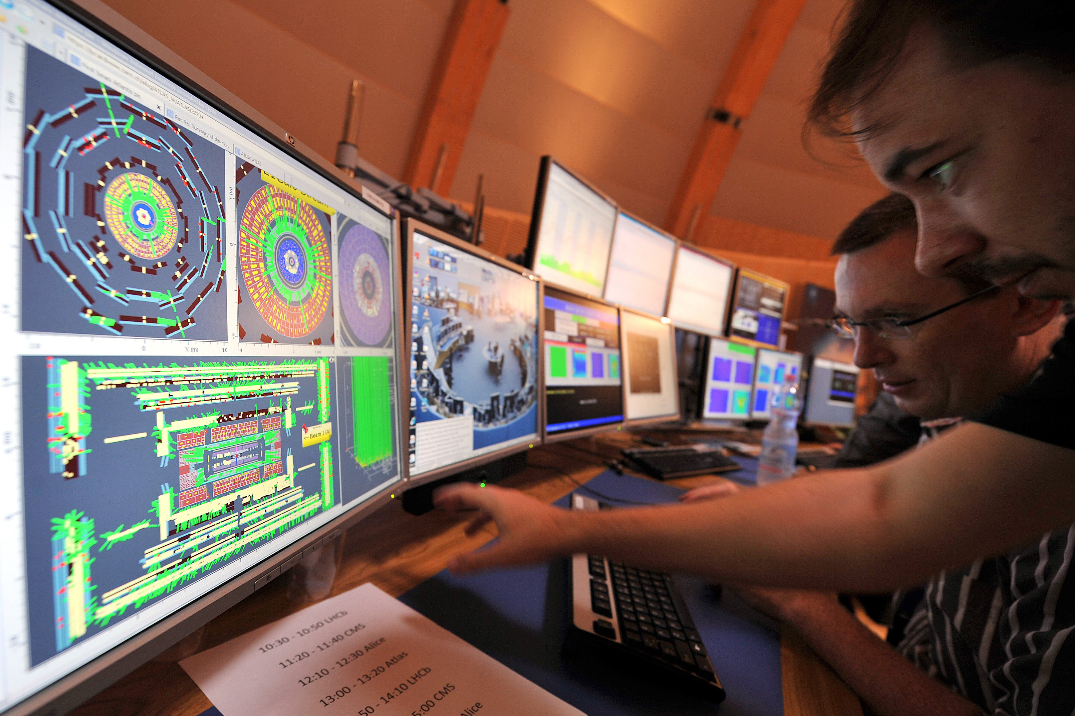 Scientists look at a computer screen at the control centre of the CERN in Geneva September 10, 2008. Scientists at the European Organisation for Nuclear Research (CERN) started up a huge particle-smashing machine on Wednesday, aiming to re-enact the conditions of the