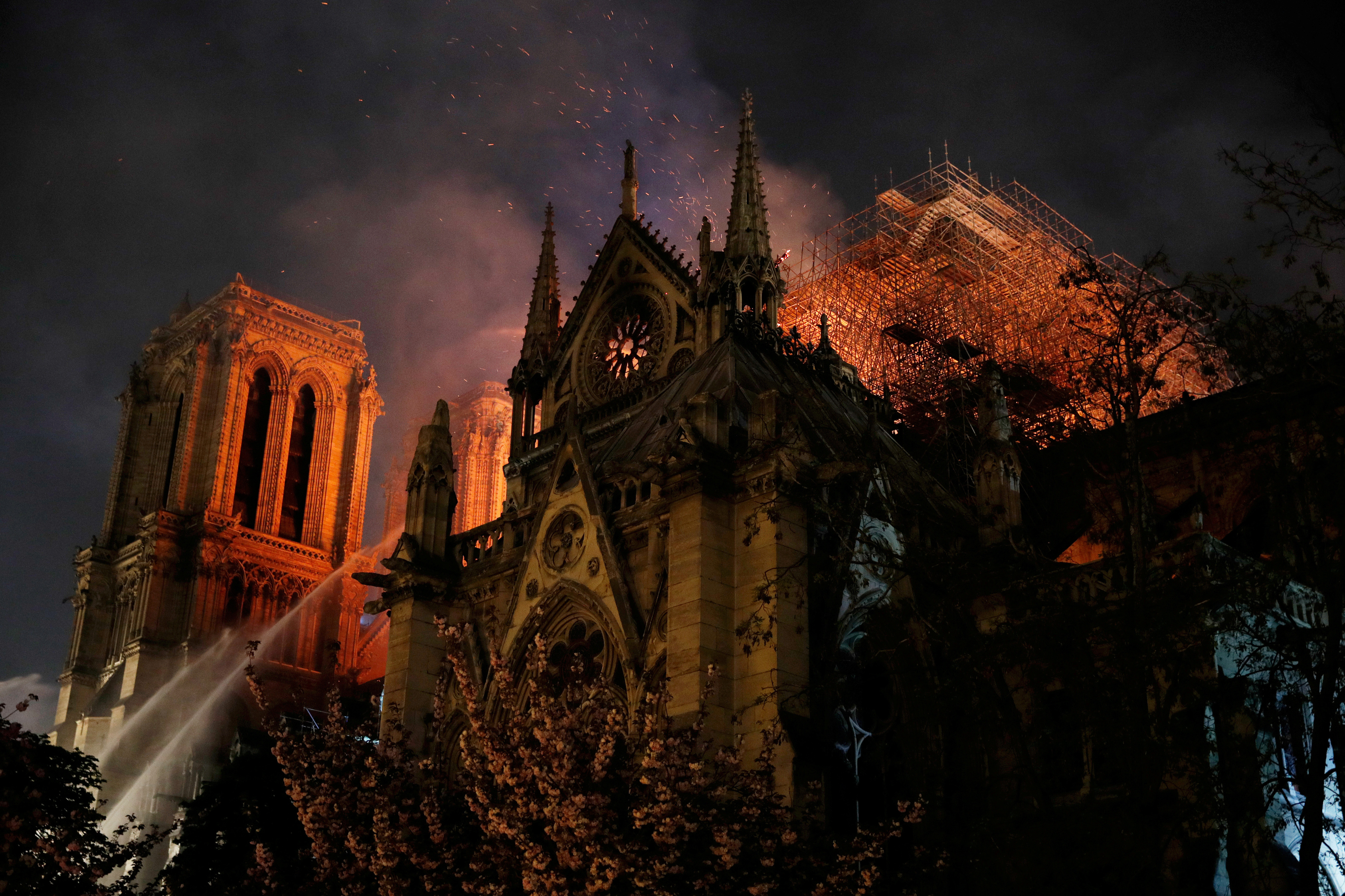 Sparks fill the air as Paris Fire brigade members spray water to extinguish flames as the Notre Dame Cathedral burns in Paris, France, April 15, 2019.   REUTERS/Philippe Wojazer      TPX IMAGES OF THE DAY - RC1FA7846930