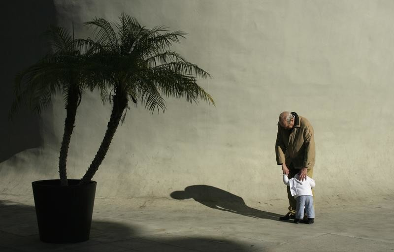 An elderly man hugs a boy in the Andalusian capital of Seville January 18, 2012.  REUTERS/Marcelo del Pozo (SPAIN - Tags: SOCIETY) - GM1E81J00GG01