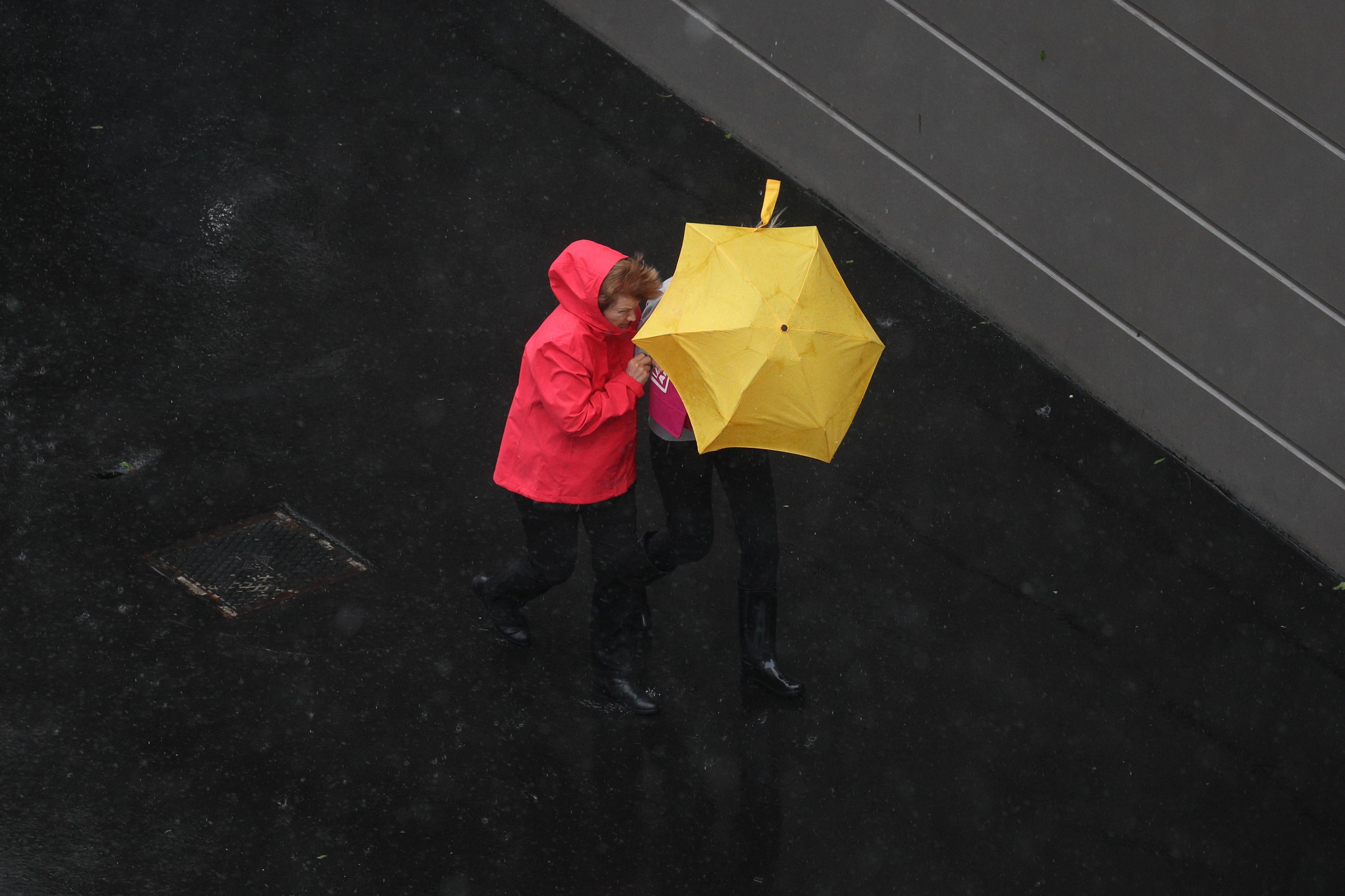 Pedestrians brave strong wind and rain in Sydney, New South Wales, Australia, February 9, 2020.  REUTERS/Loren Elliott - RC2PWE9FLNQ8