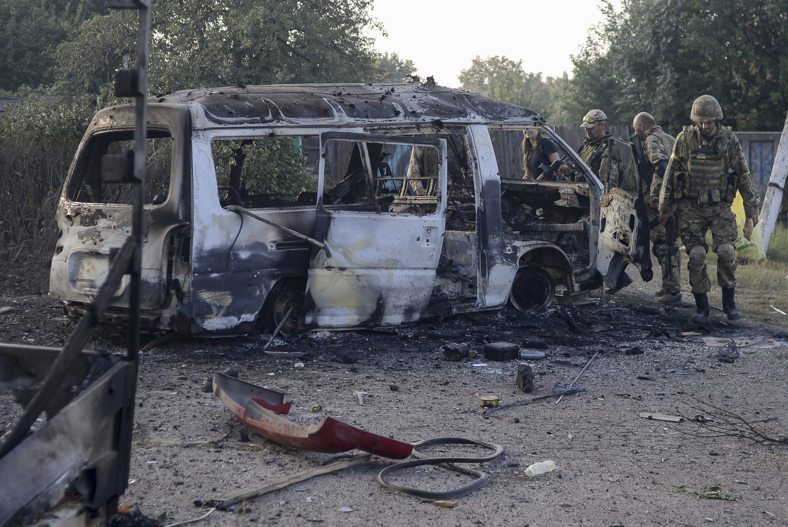 Soldiers of Ukraine's Donbas battalion inspect their unit's bus, which was destroyed in fighting, in the eastern Ukrainian town of Ilovaisk on August 24, 2014.