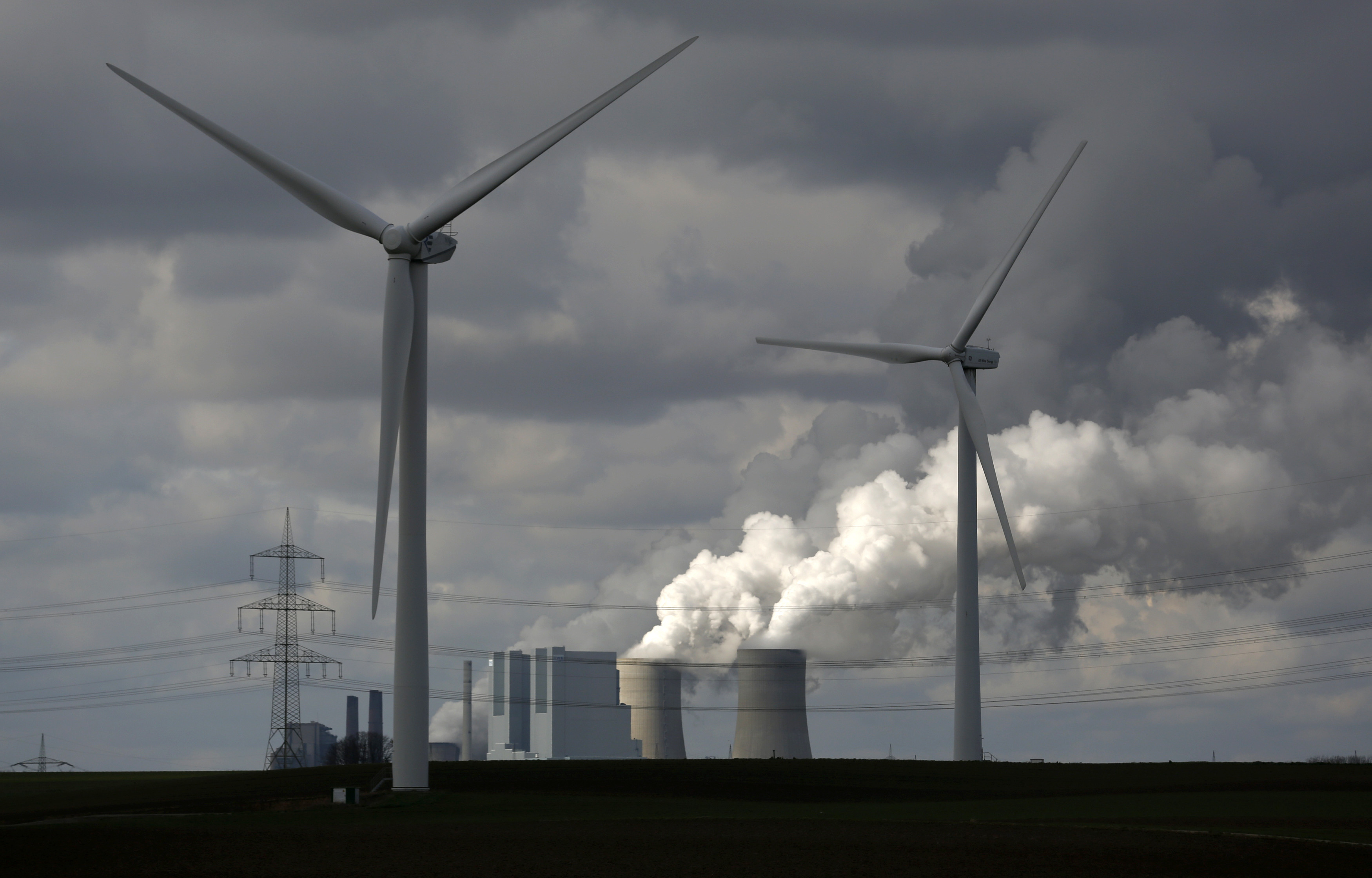 Wind turbines are seen in front of a coal power plant of German utility RWE Power near the western town of Neurath February 28, 2014. German utility RWE is set to report a net loss of almost 3 billion euros ($4 billion), the digital edition of German newspaper Handelsblatt said on Thursday, citing supervisory board sources.