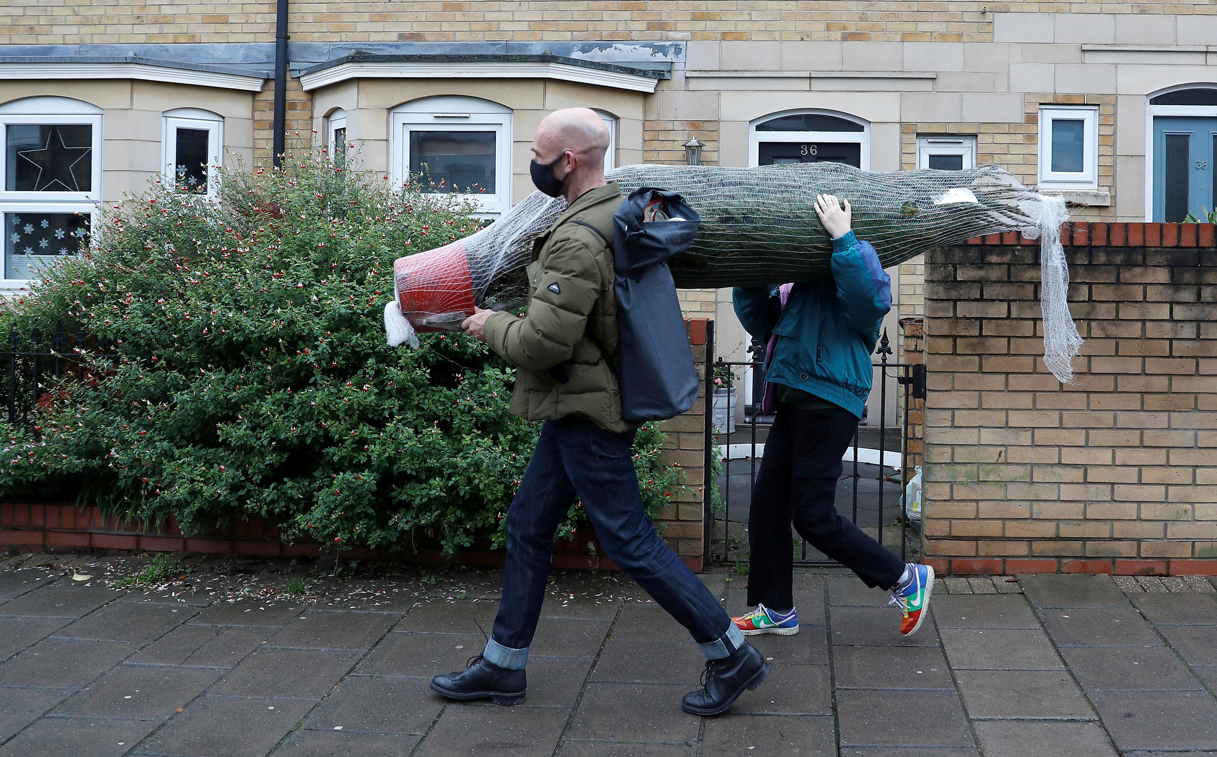 Edgar Schmitz and his daughter Greta carry their rented Christmas tree away from Christmas on The Hill in London, Britain, December 12, 2020. Picture taken December 12, 2020.