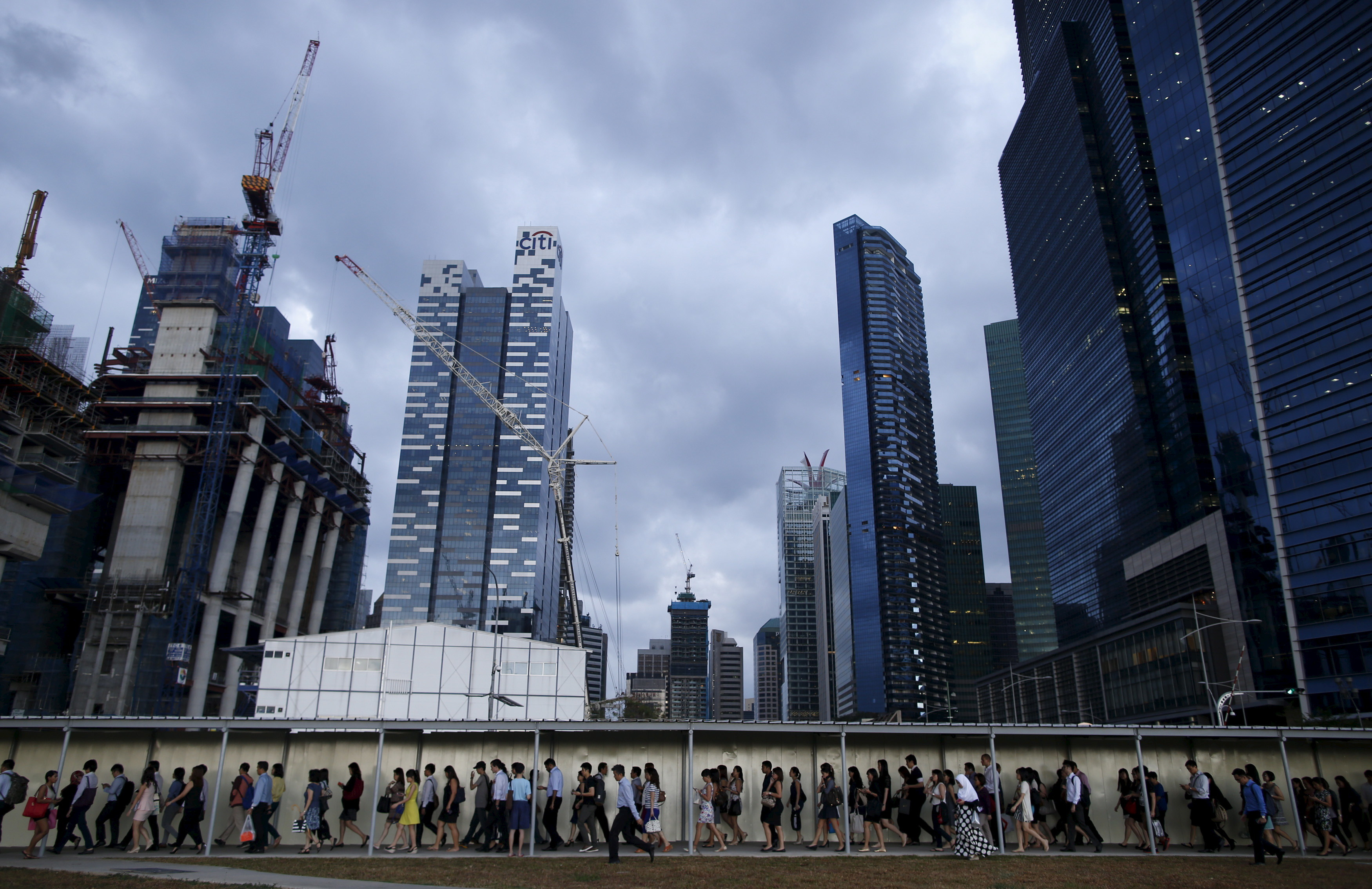 Commuters walk to the train station during evening rush hour in the financial district of Singapore March 9, 2015. When Singapore celebrated its 50th birthday as an independent country in August,the city state bore little resemblance to the tiny island nation that was expelled from Malaysia in 1965. Its physical stature has swollen by 20 percent thanks to one of the world's most aggressive land reclamation drives.  REUTERS/Edgar Su/Files  TPX IMAGES OF THE DAYPICTURE 2 OF 31 FOR WIDER IMAGE STORY 'EARTHPRINTS: SINGAPORE' SEARCH 'EARTHPRINTS SINGAPORE' FOR ALL IMAGES          - RTS7WG7