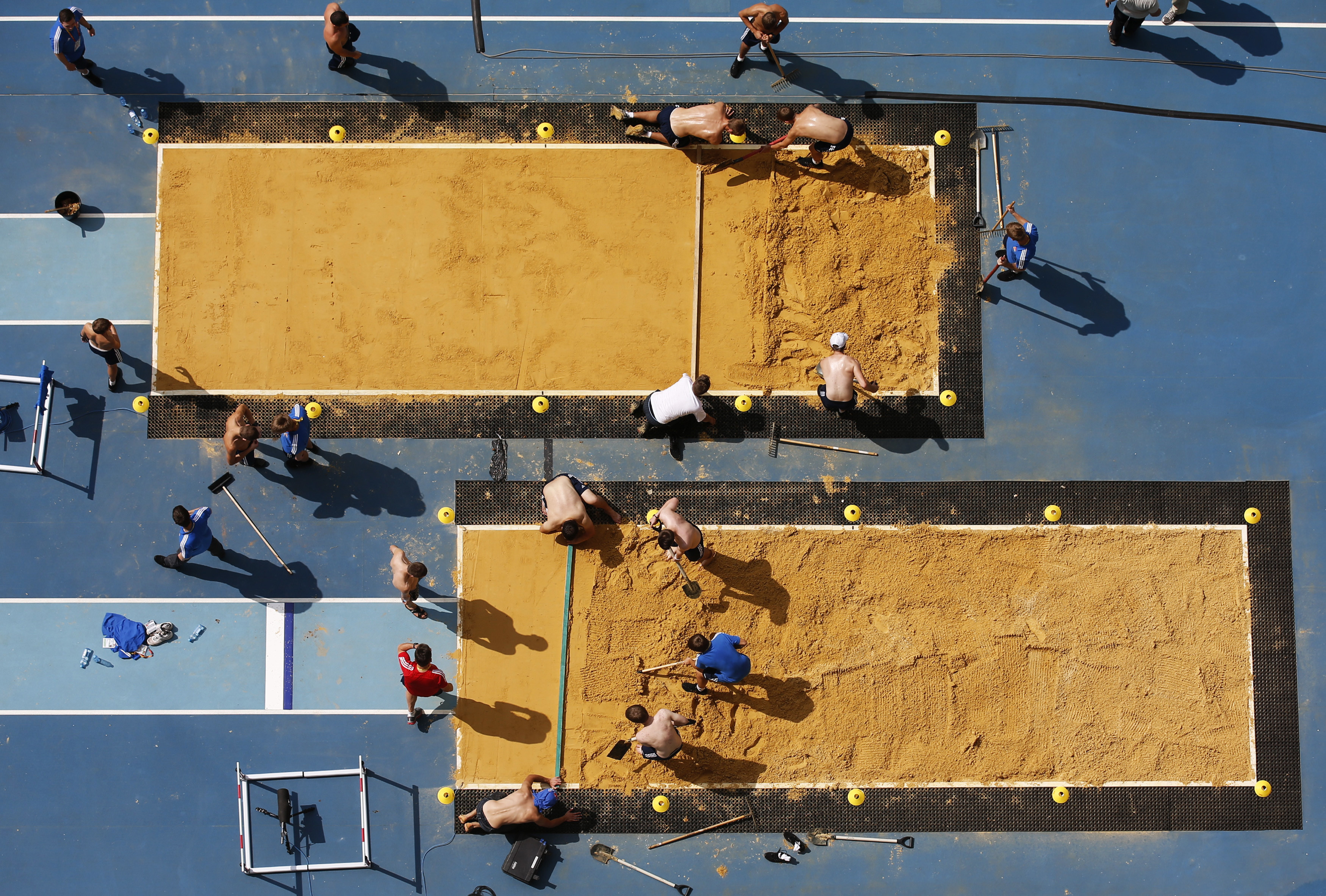 Volunteers prepare the sandpit for the 14th IAAF World Championships at the Olympic stadium in Moscow August 7, 2013. The event will be held from August 10 to 18.  REUTERS/Fabrizio Bensch (RUSSIA - Tags: SPORT ATHLETICS TPX IMAGES OF THE DAY) - RTX12COT