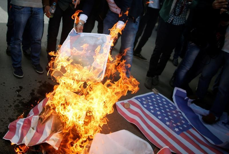 Palestinian protesters burn a poster depicting U.S. President Donald Trump and a representation of a U.S. flag during a protest against Trump's decision to recognize Jerusalem as the capital of Israel, in Gaza City December 7, 2017. REUTERS/Mohammed Salem - RC1AF0CE6AD0