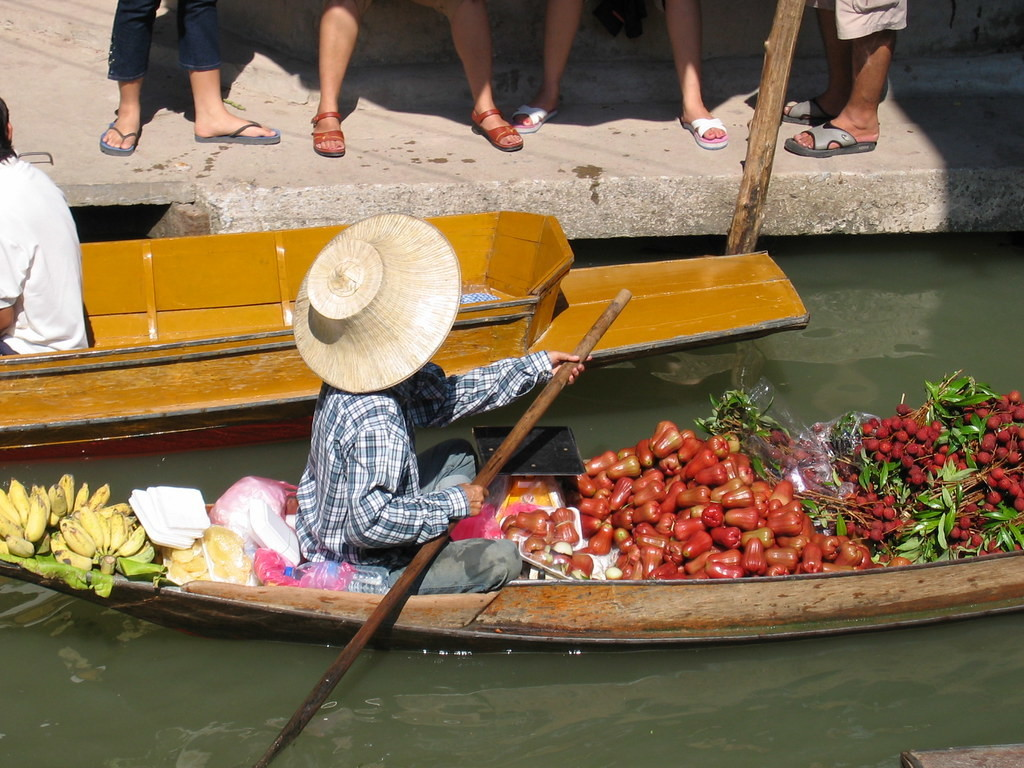 Thailand farmer rows boat laden with fruit and vegetables to market.