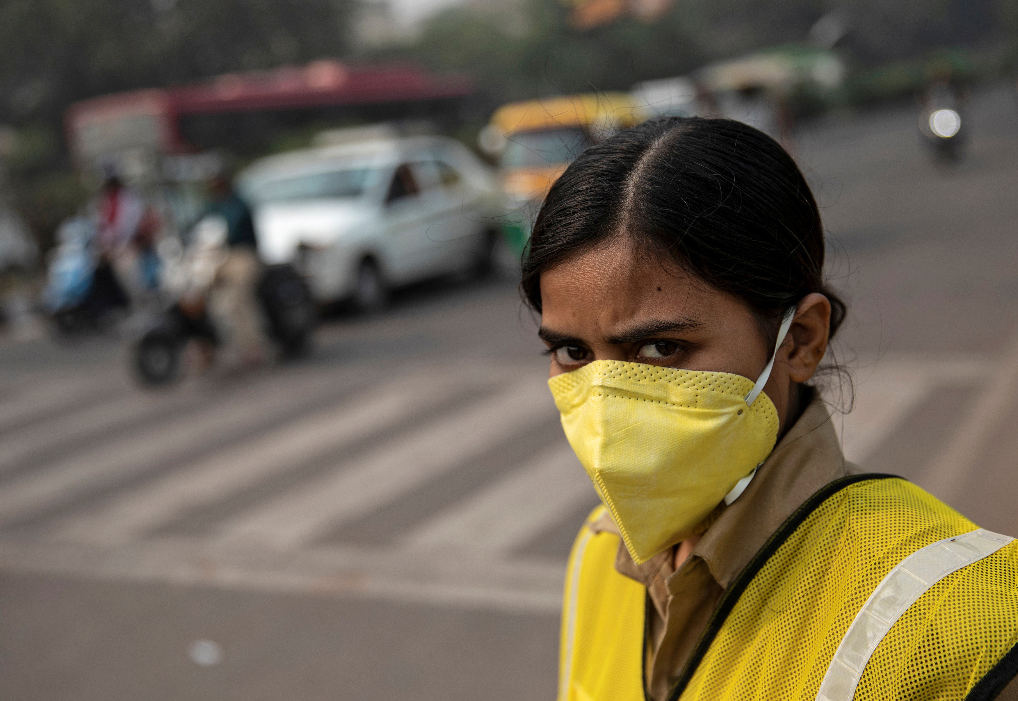 A policewoman wears a mask to protect herself from air pollution at a junction during restrictions on private vehicles based on registration plates on a smoggy morning in New Delhi, India.