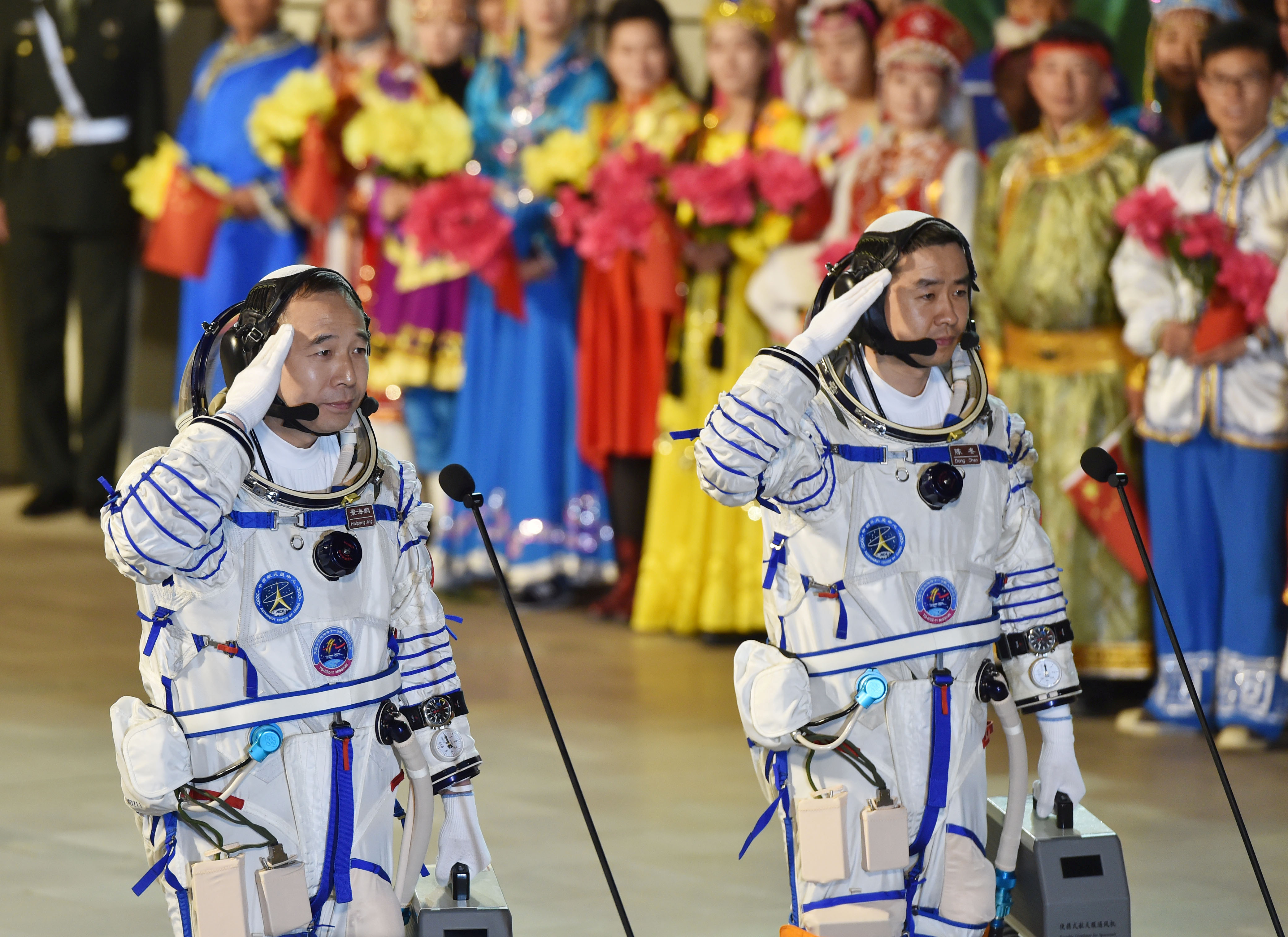 Chinese astronauts Jing Haipeng (L), Chen Dong salute before the launch of  Shenzhou-11 manned spacecraft, in Jiuquan, China, October 17, 2016. China Daily/via REUTERS ATTENTION EDITORS - THIS PICTURE WAS PROVIDED BY A THIRD PARTY. EDITORIAL USE ONLY. CHINA OUT. NO COMMERCIAL OR EDITORIAL SALES IN CHINA.    REUTERS/Stringer CHINA OUT. NO COMMERCIAL OR EDITORIAL SALES IN CHINA - RTX2P2X7