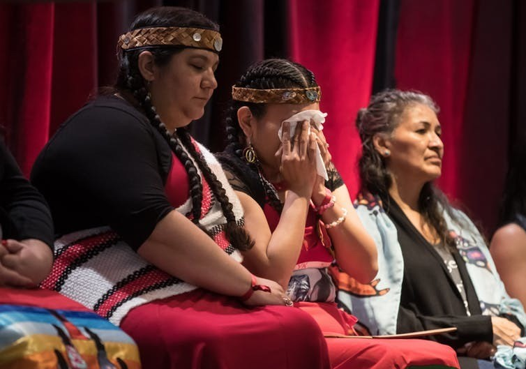 Lorelei Williams, centre, whose cousin Tanya Holyk was murdered by serial killer Robert Pickton and aunt Belinda Williams went missing in 1978, wipes away tears while seated with Rhiannon Bennett, left, and Sophie Merasty, right, after responding to the report on the National Inquiry into Missing and Murdered Indigenous Women and Girls, along with other Indigenous women and allies in Vancouver, on June 3, 2019.