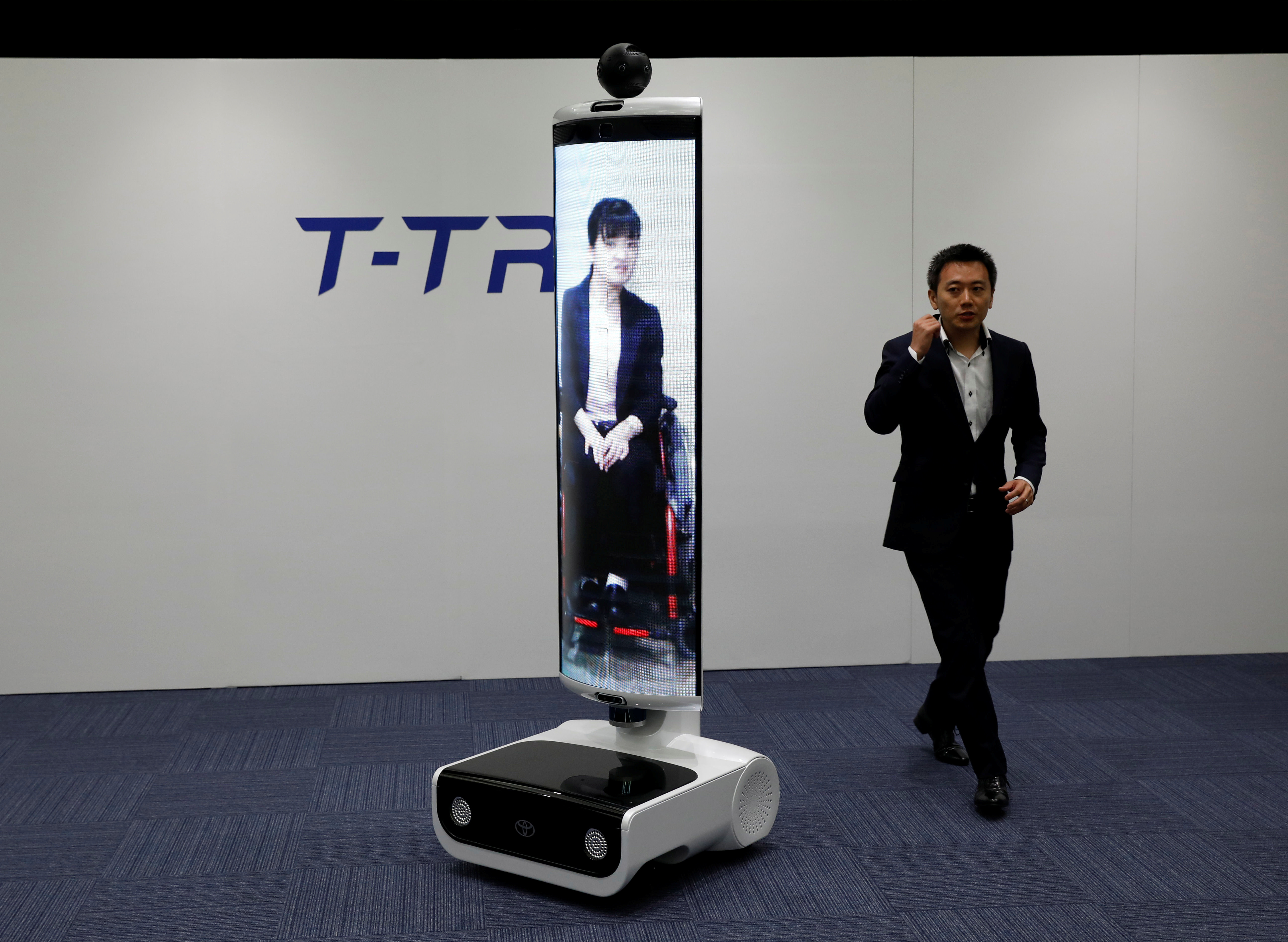 An employee of Toyota Motor Corp. demonstrates T-TR1 remote location communication robot which will be used to support the Tokyo 2020 Olympic and Paralympic Games, during a press preview in Tokyo, Japan July 18, 2019. Picture taken July 18, 2019.  REUTERS/Issei Kato - RC1B0E595880