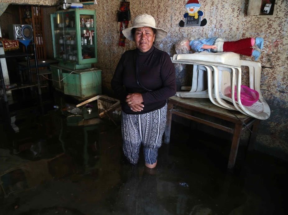 A woman cries inside her flooded house in Huarmay, a coastal region of Peru, which in 2017 saw its worst flooding in 20 years.