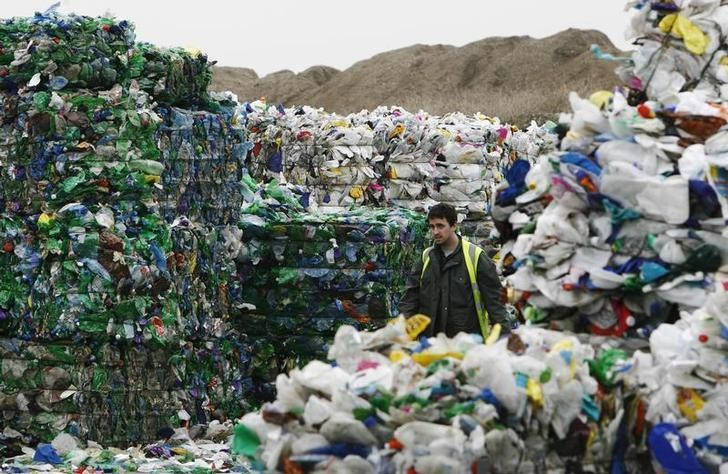 A man walks through bundles of bottles waiting to be recycled  at the Closed Loop recycling plant in Dagenham, east London February 17, 2009. Supermarkets should be made to pay more for the food packaging waste they create, local councils said on Tuesday, after a survey found almost 40 percent of it was hard to recycle.