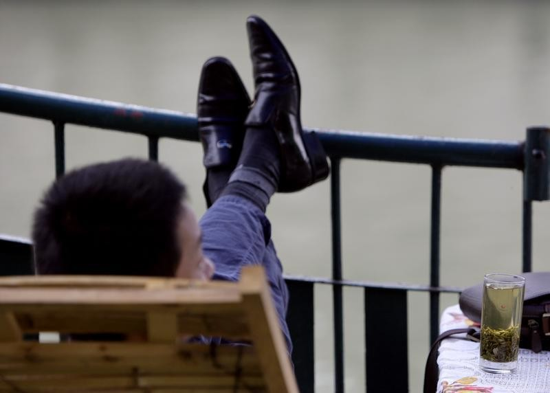 A man rests his feet on a railing as he sits in a chair with a cup of tea next to him in Chengdu September 10, 2007. Although coffee consumption is still less than one-tenth of tea consumption in China, it is becoming increasingly popular among Chinese, especially young people, because of its association with a Western lifestyle. Chinese drinks 700,000 tonnes of tea per year.       REUTERS/David Gray    (CHINA) - GM1DWCUYGSAA