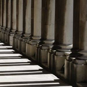 A woman walks through shadows cast by columns at the Old Royal Naval College in Greenwich east London
