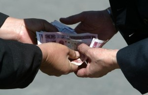 CHINESE BANKNOTES CHANGE HANDS AT MARKET IN BEIJING.