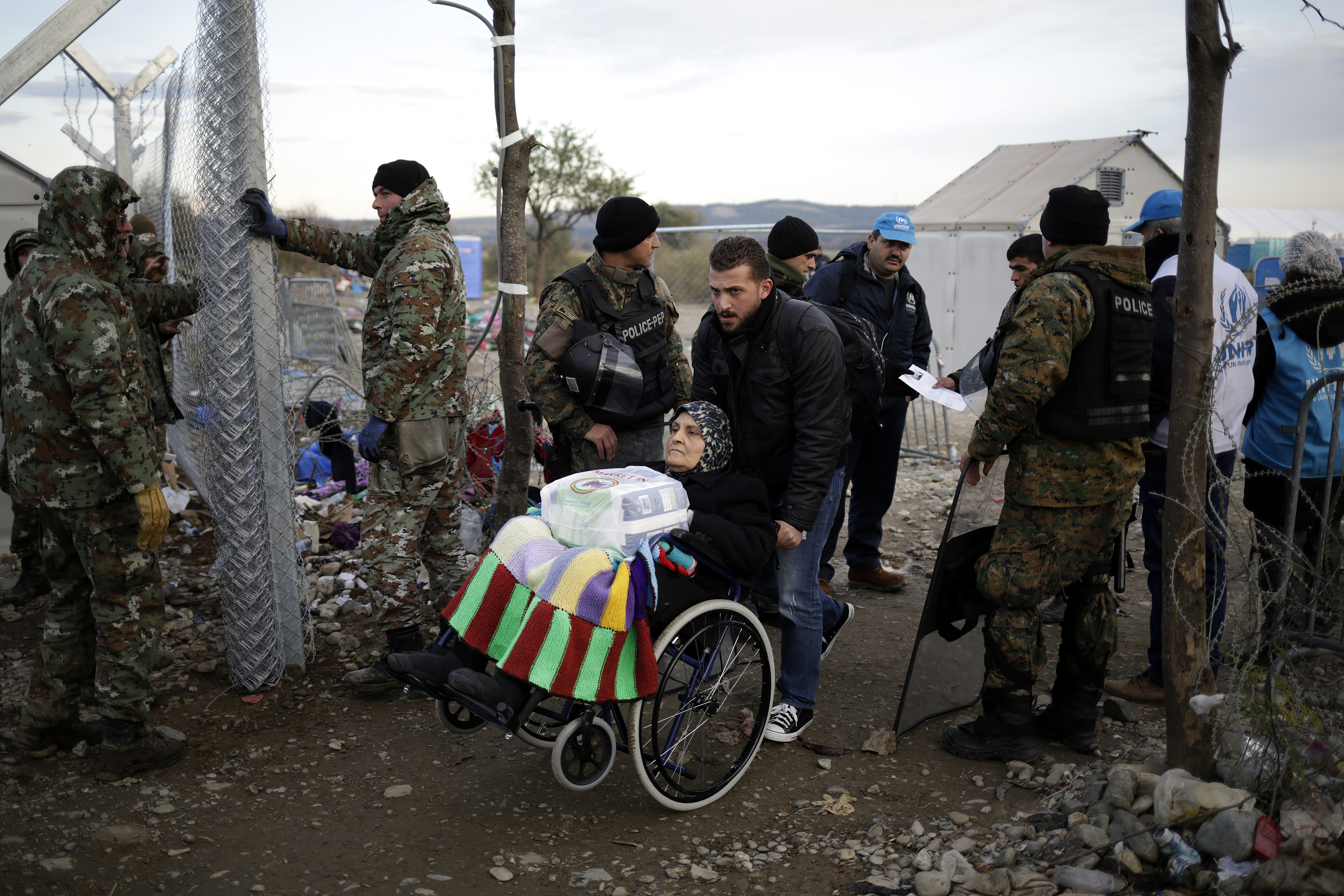 An elderly migrant in a wheelchair crosses the Macedonian-Greek border near Gevgelija, Macedonia November 28, 2015. Soldiers drove metal poles around 3 metres high into the cold, muddy ground, building a barrier similar to that erected by Hungary on its southern border to keep out the hundreds of thousands of migrants who have crossed the Balkans this year. REUTERS/Stoyan Nenov TPX IMAGES OF THE DAY - RTX1W8N3