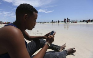 A Somali man browses the internet on his mobile phone at a beach along the Indian Ocean coastline in Mogadishu
