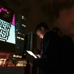 "A boy uses an iPad to play a game, which is projected onto the Fiesp building, during the ""Play!"" exhibition in Avenida Paulista"