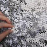 An employee of puzzle maker Beverly holds a piece of the company's white micro 1000 piece jigsaw puzzle at the International Toy Show in Tokyo