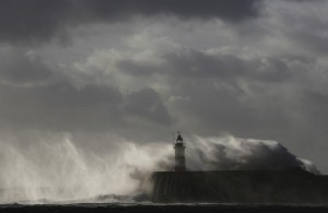 Waves crash against a lighthouse during storms that battered Britain and where a 14-year-old boy was swept away to sea, at Newhaven in South East England